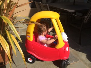 """My daughter happily playing in her Little Tikes """"car."""""""